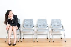 Επιχειρησιακή θηλυκή πρότυπη συνεδρίαση στην ξύλινη καρέκλα πατωμάτων Στοκ Εικόνα