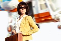 Επιχειρησιακή κυρία με την περίπτωση και το πετώντας ελικόπτερο Στοκ Φωτογραφία