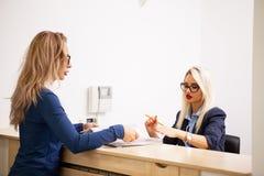 Επιχειρησιακή κυρία με τον ξανθό γραμματέα της στην περιμένοντας περιοχή του α Στοκ Εικόνες