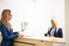 Επιχειρησιακή κυρία με τον ξανθό γραμματέα της στην περιμένοντας περιοχή του α Στοκ εικόνα με δικαίωμα ελεύθερης χρήσης