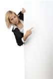 Επιχειρησιακή κυρία που κοιτάζει από τον άσπρο πίνακα διαφημίσεων Στοκ Εικόνες