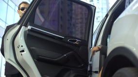 Επιχειρησιακή κυρία που παίρνει στο αυτοκίνητο πολυτέλειας, ανοίγοντας πόρτα οδηγών για τη γυναίκα, άποψη βάσεων απόθεμα βίντεο