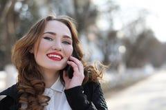Επιχειρησιακή κυρία σε ένα κοστούμι υπαίθρια με το κινητό τηλέφωνο στοκ εικόνες
