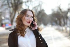 Επιχειρησιακή κυρία σε ένα κοστούμι υπαίθρια με το κινητό τηλέφωνο στοκ εικόνα με δικαίωμα ελεύθερης χρήσης