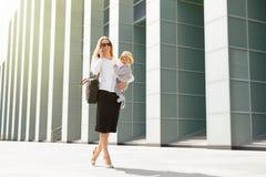Επιχειρησιακή μητέρα στην πόλη με το μωρό στα χέρια της Στοκ εικόνες με δικαίωμα ελεύθερης χρήσης