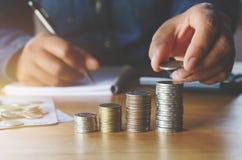 επιχειρησιακή λογιστική με τα χρήματα αποταμίευσης με το χέρι που βάζει τα νομίσματα επάνω στοκ εικόνα με δικαίωμα ελεύθερης χρήσης