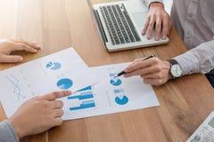 Επιχειρησιακή ομάδα δύο συνάδελφοι που συζητούν τη νέα οικονομική γραφική παράσταση σχεδίων Στοκ Εικόνες