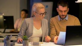 Επιχειρησιακή ομάδα με το lap-top που λειτουργεί τη νύχτα το γραφείο απόθεμα βίντεο