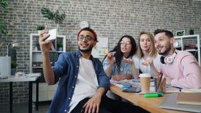 Επιχειρησιακή ομάδα που κάνει την τηλεοπτική κλήση με το smartphone που καλεί από την ομιλία γραφείων απόθεμα βίντεο