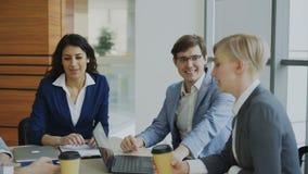 Επιχειρησιακή ομάδα που κουβεντιάζει καθμένος στο σύγχρονο γραφείο στο εσωτερικό κατά τη διάρκεια του διαλείμματος φιλμ μικρού μήκους