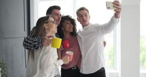 Επιχειρησιακή ομάδα που παίρνει ένα selfie στο σπάσιμο γραφείων απόθεμα βίντεο