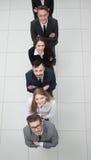 Επιχειρησιακή ομάδα που στέκεται σε μια στήλη σε ένα άσπρο υπόβαθρο Στοκ Φωτογραφίες