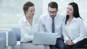 Επιχειρησιακή ομάδα που συζητά τις πληροφορίες με το lap-top στην αρχή Στοκ Φωτογραφία