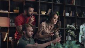 Επιχειρησιακή ομάδα που συζητά το νέο πρόγραμμα για τη οθόνη υπολογιστή στο άνετο γραφείο απόθεμα βίντεο