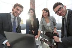 Επιχειρησιακή ομάδα σε μια συνεδρίαση σε μια σύγχρονη φωτεινή κεντρική εργασία γραφείων Στοκ Εικόνα