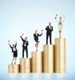 Επιχειρησιακή ομάδα με τα φλυτζάνια που στέκονται στα σκαλοπάτια των χρυσών νομισμάτων Στοκ Φωτογραφίες