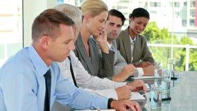 Επιχειρησιακή ομάδα που παίρνει τις σημειώσεις κατά τη διάρκεια της διάσκεψης ενώ συνάδελφος που έχει ένα τηλεφώνημα απόθεμα βίντεο