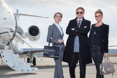 Επιχειρησιακή ομάδα που στέκεται μπροστά από το ιδιωτικό αεριωθούμενο αεροπλάνο Στοκ εικόνες με δικαίωμα ελεύθερης χρήσης