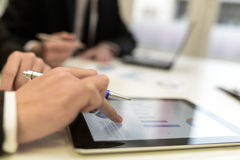 Επιχειρησιακή ομάδα που χρησιμοποιεί τον υπολογιστή ταμπλετών για να εργαστεί με τα οικονομικά στοιχεία Στοκ Φωτογραφίες