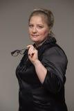 Επιχειρησιακή παχιά γυναίκα σε ένα κοστούμι που κρατά τα γυαλιά για το όραμα Στοκ Εικόνα