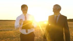 Επιχειρησιακή συνεδρίαση με τον εργαζόμενο συνεργάτη στο πάρκο στο ηλιοβασίλεμα Οι επιχειρηματίες συζητούν το σχέδιο ομαδικής εργ απόθεμα βίντεο