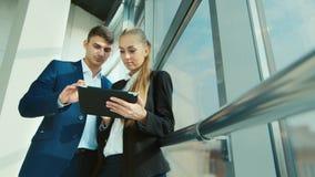 Επιχειρησιακή συνεδρίαση των συναδέλφων Χρησιμοποιήστε μια ταμπλέτα, επικοινωνήστε στα πλαίσια ενός μεγάλου παραθύρου στο γραφείο απόθεμα βίντεο