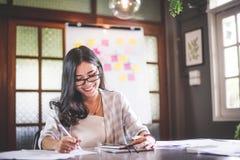 Επιχειρησιακή όμορφη ασιατική γυναίκα που εργάζεται και σημείωση γραψίματος Στοκ Εικόνες