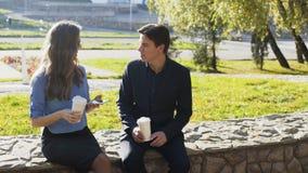 Επιχειρησιακοί άνδρας και γυναίκα που διοργανώνουν τη συνεδρίαση και τη συνομιλία υπαίθριες φιλμ μικρού μήκους