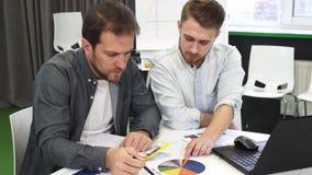 Επιχειρησιακοί συνάδελφοι αρσενικών που κάνουν τη γραφική εργασία μαζί στο γραφείο απόθεμα βίντεο