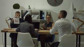 Επιχειρησιακοί συνάδελφοι που εργάζονται στο γραφείο ανοιχτού χώρου απόθεμα βίντεο