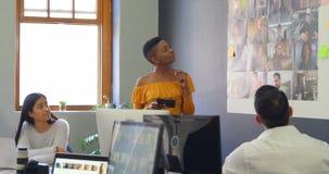 Επιχειρησιακοί συνάδελφοι που συζητούν πέρα από τις φωτογραφίες στη συνεδρίαση 4k απόθεμα βίντεο