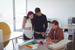 Επιχειρησιακοί συνάδελφοι που συζητούν πέρα από swatch χρώματος στο δημιουργικό γραφείο Στοκ Εικόνες