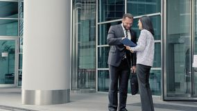Επιχειρησιακός άνδρας που χαιρετά μια νέα γυναίκα στην είσοδο στο κτίριο γραφείων φιλμ μικρού μήκους