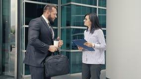 Επιχειρησιακός άνδρας που χαιρετά μια νέα γυναίκα στην είσοδο στο κτίριο γραφείων απόθεμα βίντεο