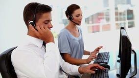 Επιχειρησιακός άνδρας και επιχειρησιακή γυναίκα σε ένα κέντρο κλήσης απόθεμα βίντεο