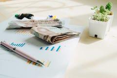 Επιχειρησιακός εξοπλισμός με τη μάνδρα και χρήματα που τοποθετούνται στις πληροφορίες pape Στοκ Εικόνες