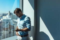 Επιχειρησιακός επενδυτής που υπερασπίζεται ένα παράθυρο στην αρχή Στοκ Εικόνες