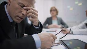 Επιχειρησιακός εργαζόμενος που αισθάνεται τον κακό πονοκέφαλο στη συνεδρίαση, την απογοήτευση εργασίας και την πίεση απόθεμα βίντεο