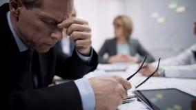 Επιχειρησιακός εργαζόμενος που αισθάνεται τον κακό πονοκέφαλο στη συνεδρίαση, την απογοήτευση εργασίας και την πίεση στοκ εικόνες με δικαίωμα ελεύθερης χρήσης