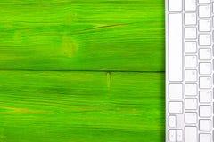 Επιχειρησιακός εργασιακός χώρος με τον υπολογιστή, ασύρματο πληκτρολόγιο, κλειδιά στο παλαιό πράσινο ξύλινο επιτραπέζιο υπόβαθρο  Στοκ φωτογραφία με δικαίωμα ελεύθερης χρήσης
