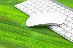 Επιχειρησιακός εργασιακός χώρος με τον υπολογιστή, ασύρματο πληκτρολόγιο, κλειδιά στο παλαιό πράσινο ξύλινο επιτραπέζιο υπόβαθρο  Στοκ φωτογραφίες με δικαίωμα ελεύθερης χρήσης