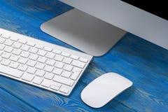 Επιχειρησιακός εργασιακός χώρος με τον υπολογιστή, το ασύρματα πληκτρολόγιο και το ποντίκι στο παλαιό σκοτεινό ξύλινο επιτραπέζιο Στοκ φωτογραφίες με δικαίωμα ελεύθερης χρήσης