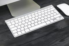 Επιχειρησιακός εργασιακός χώρος με τον υπολογιστή, το ασύρματα πληκτρολόγιο και το ποντίκι στο μαύρο ξύλινο επιτραπέζιο υπόβαθρο  Στοκ Φωτογραφία