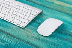 Επιχειρησιακός εργασιακός χώρος με τον υπολογιστή, το ασύρματα πληκτρολόγιο και το ποντίκι στο παλαιό μπλε ξύλινο επιτραπέζιο υπό Στοκ Εικόνα