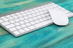 Επιχειρησιακός εργασιακός χώρος με τον υπολογιστή, το ασύρματα πληκτρολόγιο και το ποντίκι στο παλαιό μπλε ξύλινο επιτραπέζιο υπό Στοκ Φωτογραφίες