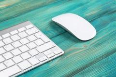 Επιχειρησιακός εργασιακός χώρος με τον υπολογιστή, το ασύρματα πληκτρολόγιο και το ποντίκι στο παλαιό μπλε ξύλινο επιτραπέζιο υπό Στοκ φωτογραφία με δικαίωμα ελεύθερης χρήσης
