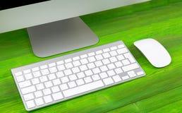 Επιχειρησιακός εργασιακός χώρος με τον υπολογιστή, το ασύρματα πληκτρολόγιο και το ποντίκι στο παλαιό πράσινο ξύλινο επιτραπέζιο  Στοκ Εικόνα