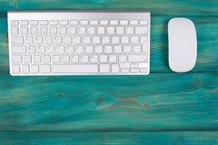 Επιχειρησιακός εργασιακός χώρος με τον υπολογιστή, το ασύρματα πληκτρολόγιο και το ποντίκι στο παλαιό μπλε ξύλινο επιτραπέζιο υπό Στοκ Φωτογραφία