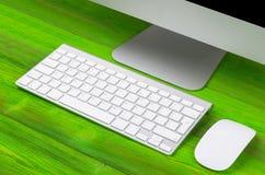 Επιχειρησιακός εργασιακός χώρος με τον υπολογιστή, το ασύρματο πληκτρολόγιο, τα κλειδιά και το ποντίκι στο παλαιό πράσινο ξύλινο  Στοκ Φωτογραφίες