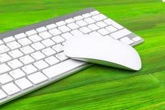Επιχειρησιακός εργασιακός χώρος με τον υπολογιστή, το ασύρματο πληκτρολόγιο, τα κλειδιά και το ποντίκι στο παλαιό πράσινο ξύλινο  Στοκ Εικόνα